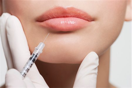 Close up of woman receiving botox injection in lips Stock Photo - Premium Royalty-Free, Code: 635-06045626