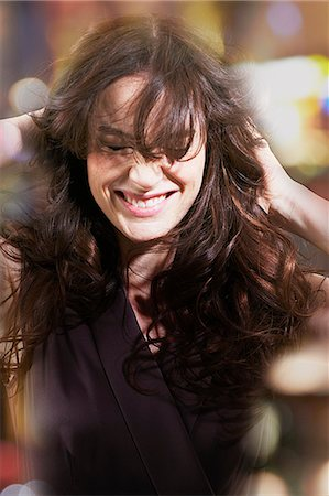 Woman with hands in hair laughing Stock Photo - Premium Royalty-Free, Code: 635-06045638