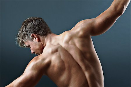 Rear view of bare chested man with arms outstretched Stock Photo - Premium Royalty-Free, Code: 635-06045630