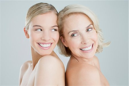 Smiling mother and daughter back to back Stock Photo - Premium Royalty-Free, Code: 635-06045640