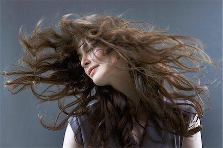 Smiling woman flipping hair Stock Photo - Premium Royalty-Free, Code: 635-06045650