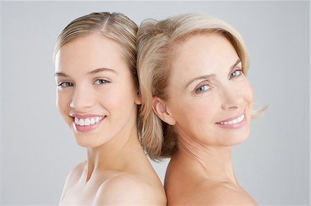 Portrait of smiling mother and daughter back to back Stock Photo - Premium Royalty-Free, Code: 635-06045666