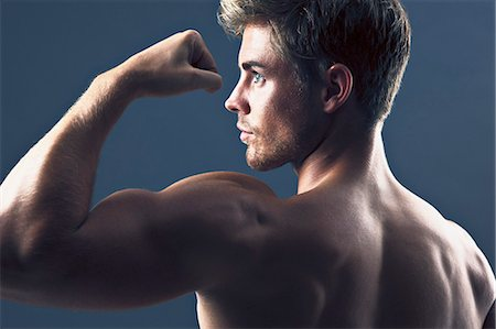 Rear view portrait of man flexing biceps muscles Stock Photo - Premium Royalty-Free, Code: 635-06045674