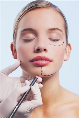 Close up of woman's face being marked with dotted lines Stock Photo - Premium Royalty-Free, Code: 635-06045673