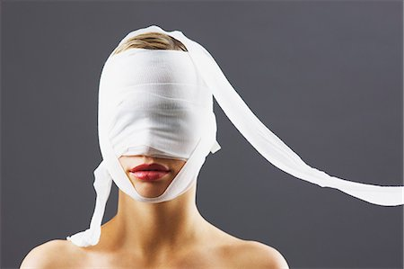 Bandage covering woman's face Stock Photo - Premium Royalty-Free, Code: 635-06045687