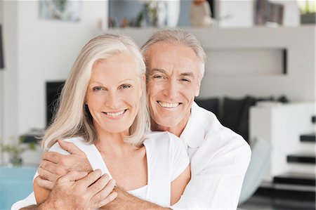 Portrait of smiling couple hugging in living room Stock Photo - Premium Royalty-Free, Code: 635-06191512