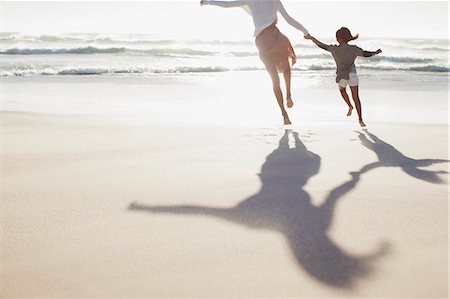southeast asian ethnicity - Mother and daughter holding hands and running on sunny beach Stock Photo - Premium Royalty-Free, Code: 635-06191618