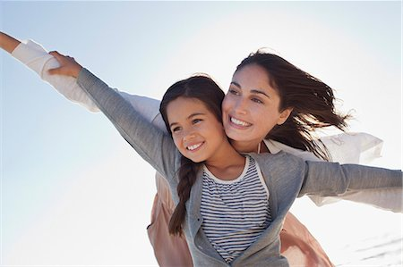 flying happy woman images - Smiling mother and daughter with arms outstretched on beach Stock Photo - Premium Royalty-Free, Code: 635-06191631