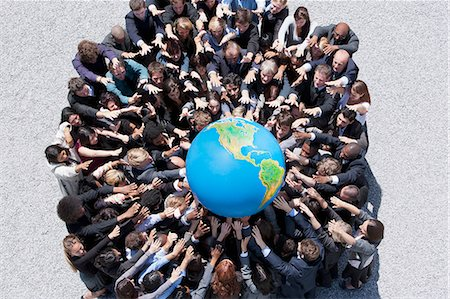 Crowd of business people in huddle reaching for globe Stock Photo - Premium Royalty-Free, Code: 635-06191676