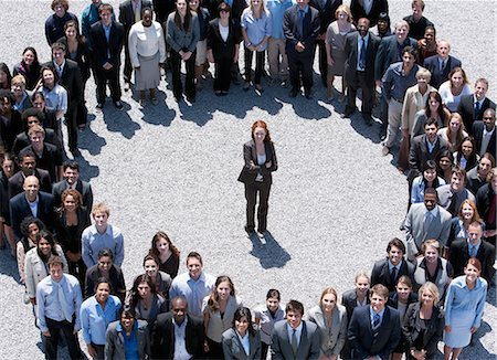Portrait of businesswoman standing at center of circle formed by business people Stock Photo - Premium Royalty-Free, Code: 635-06191679