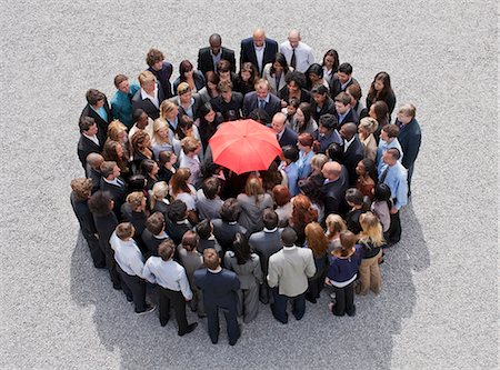 Umbrella at center of circle formed by business people Stock Photo - Premium Royalty-Free, Code: 635-06191687