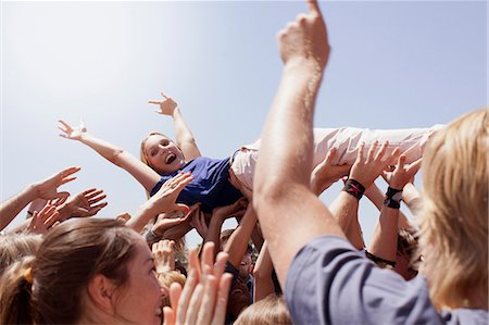 Enthusiastic woman crowd surfing Stock Photo - Premium Royalty-Free, Code: 635-06191681