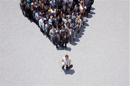 Businessman at apex of pyramid formed by crowd Stock Photo - Premium Royalty-Free, Code: 635-06191682