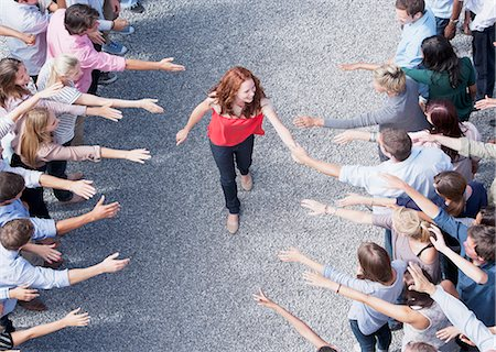 Woman walking through crowd with arms outstretched Stock Photo - Premium Royalty-Free, Code: 635-06191694