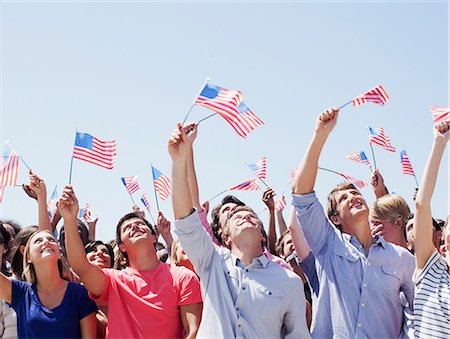 Smiling people waving American flags and looking up in crowd Stock Photo - Premium Royalty-Free, Code: 635-06191691