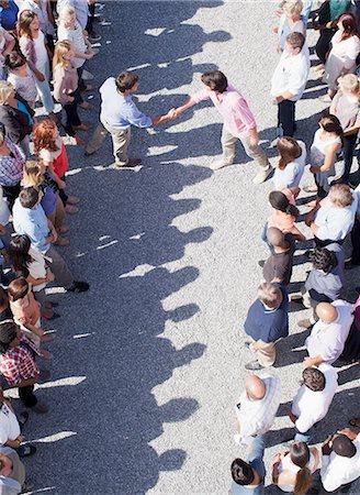 Men handshaking between separate groups Stock Photo - Premium Royalty-Free, Code: 635-06191705