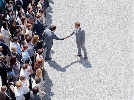 Businessman shaking man's hand in crowd Stock Photo - Premium Royalty-Free, Code: 635-06191706