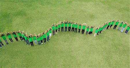 Portrait of people in green t-shirts forming wavy line in field Foto de stock - Royalty Free Premium, Número: 635-06191700