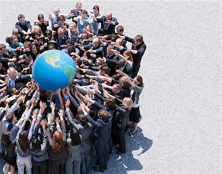 partnership - Crowd of business people in huddle reaching for globe Stock Photo - Premium Royalty-Free, Code: 635-06191716