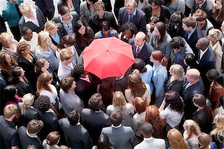 Red umbrella at center of business people in huddle Stock Photo - Premium Royalty-Free, Code: 635-06191721