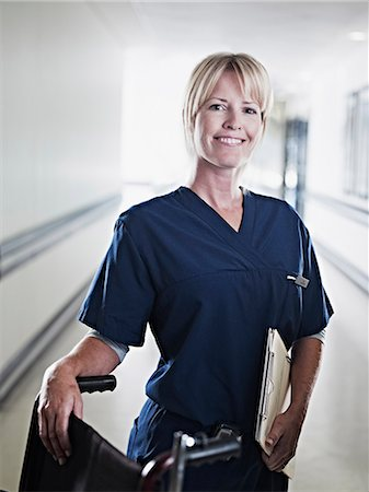 Serious nurse standing in hospital corridor with medical record and wheelchair Stock Photo - Premium Royalty-Free, Code: 635-06191887