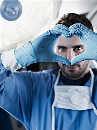 Portrait of surgeon making heart-shape with hands under surgical light Stock Photo - Premium Royalty-Free, Code: 635-06191880