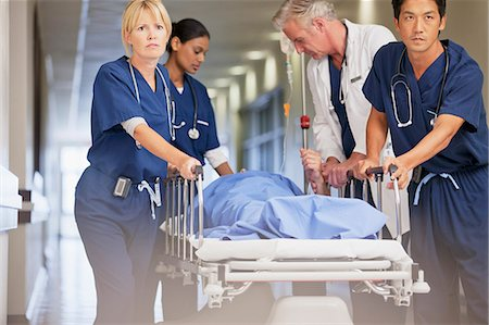 patient walking hospital halls - Doctor and nurses wheeling patient in gurney down hospital corridor Stock Photo - Premium Royalty-Free, Code: 635-06191934
