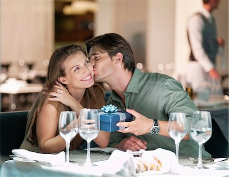 Man kissing and giving gift to woman in restaurant Stock Photo - Premium Royalty-Free, Code: 635-06192011