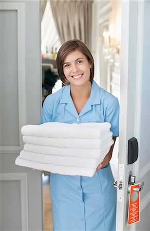 Portrait of smiling maid with towels in hotel room doorway Stock Photo - Premium Royalty-Free, Code: 635-06192025