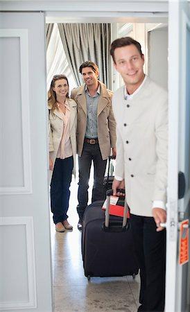 Portrait of bellman opening hotel room door with couple in background Stock Photo - Premium Royalty-Free, Code: 635-06192022