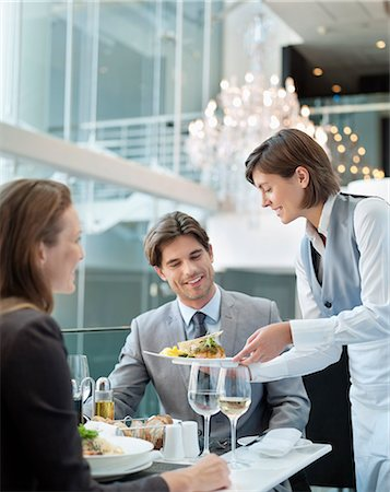Waitress serving food to couple in restaurant Stock Photo - Premium Royalty-Free, Code: 635-06192039