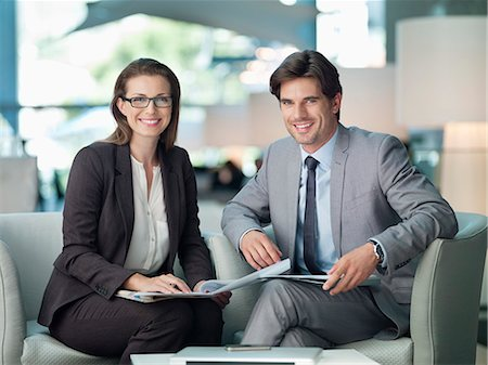 Portrait of smiling businessman and businesswoman working in lobby Stock Photo - Premium Royalty-Free, Code: 635-06192030