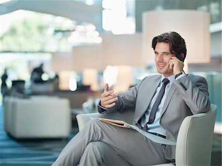 Smiling businessman talking on cell phone in lobby Stock Photo - Premium Royalty-Free, Code: 635-06192044