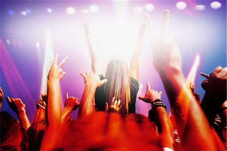 Stage lights shining on audience with arms raised at music concert Stock Photo - Premium Royalty-Free, Code: 635-06192045