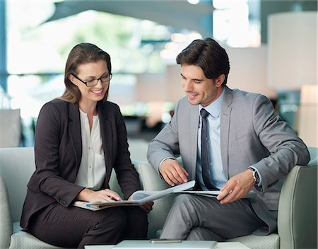 Businessman and businesswoman working in lobby Stock Photo - Premium Royalty-Free, Code: 635-06192040