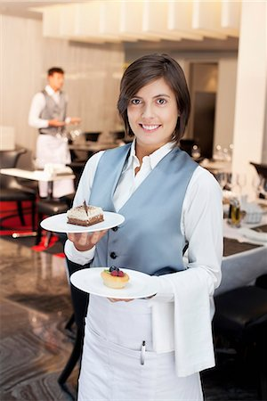 Portrait of smiling waitress holding desserts in restaurant Stock Photo - Premium Royalty-Free, Code: 635-06192041