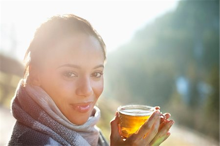 Portrait of smiling woman in scarf drinking cider Stock Photo - Premium Royalty-Free, Code: 635-06192057