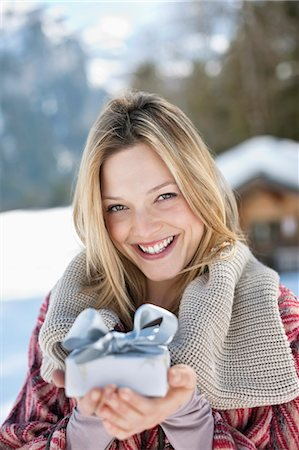 present wrapped close up - Portrait of smiling woman holding Christmas gift in snow Stock Photo - Premium Royalty-Free, Code: 635-06192060