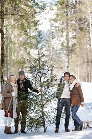 snow christmas tree white - Portrait of smiling couples with fresh cut Christmas tree in woods Stock Photo - Premium Royalty-Free, Code: 635-06192062