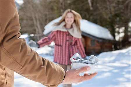 Woman running toward man holding Christmas gift in snow Stock Photo - Premium Royalty-Free, Code: 635-06192086