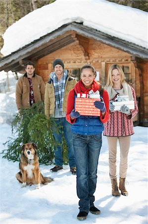 snow christmas tree white - Portrait of smiling couples and dog with fresh cut Christmas tree and gifts in front of cabin Stock Photo - Premium Royalty-Free, Code: 635-06192104