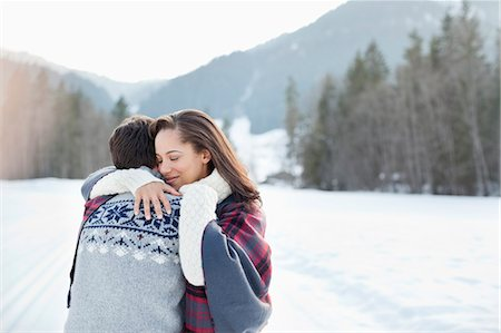 Smiling woman hugging man in snowy field Stock Photo - Premium Royalty-Free, Code: 635-06192115