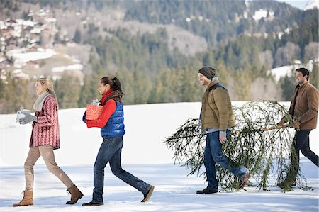 snow christmas tree white - Couples and dog carrying fresh cut Christmas tree and gifts in snow Stock Photo - Premium Royalty-Free, Code: 635-06192110