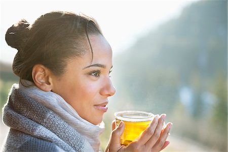 Close up of smiling woman drinking tea outdoors Stock Photo - Premium Royalty-Free, Code: 635-06192125