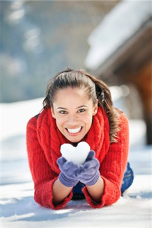Portrait of smiling woman holding heart-shaped snowball Stock Photo - Premium Royalty-Free, Code: 635-06192123