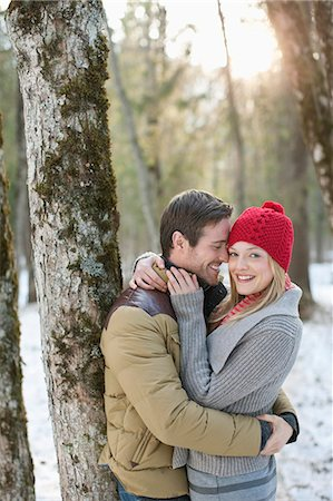 Portrait of smiling couple hugging in snowy woods Stock Photo - Premium Royalty-Free, Code: 635-06192144