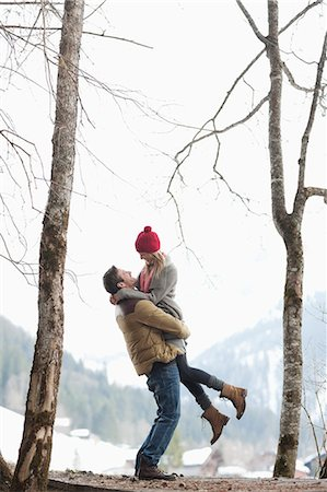 Man lifting woman in snowy woods Stock Photo - Premium Royalty-Free, Code: 635-06192178