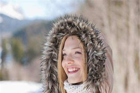 fur - Smiling woman wearing fur hood Stock Photo - Premium Royalty-Free, Code: 635-06192189