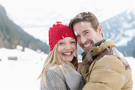 Portrait of smiling couple hugging in snow Stock Photo - Premium Royalty-Free, Code: 635-06192215