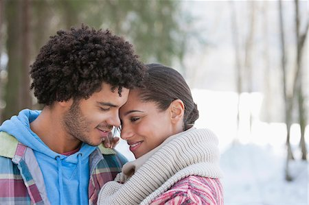 Smiling couple hugging face to face in snowy woods Stock Photo - Premium Royalty-Free, Code: 635-06192217